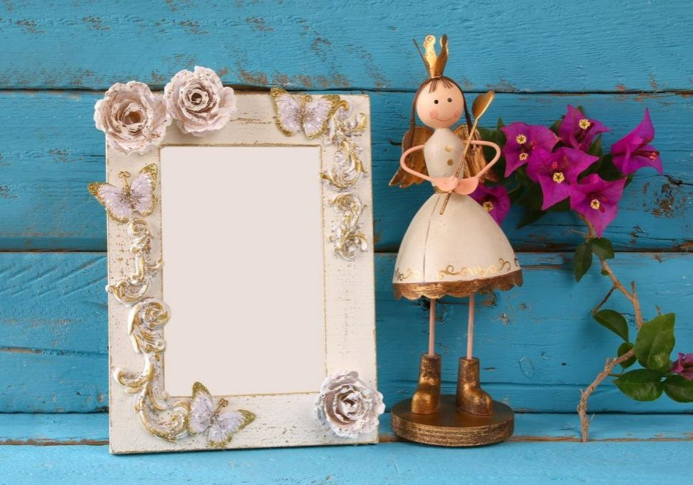 image of white vintage blank frame and cute fairy princess on wooden table.