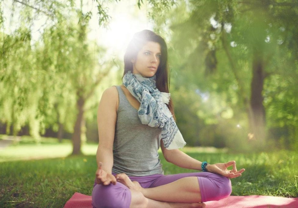 Portrait of beautiful mixed race caucasian, african, middle eastern girl meditating and doing yoga at sunset on the grass in a park or forrest