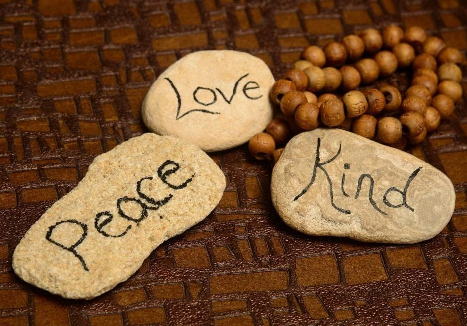 peace, love and kindness words on rocks for world peace