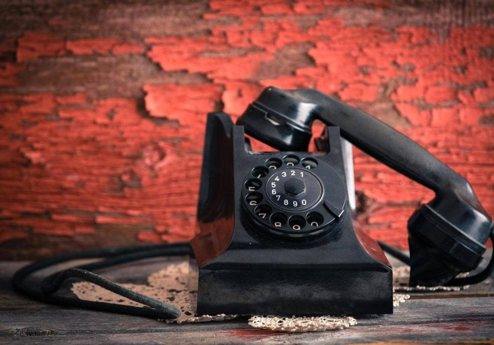 Old-fashioned rotary telephone with the handset off the hook effectively blocking the line against a rustic wall with distressed peeling red paint
